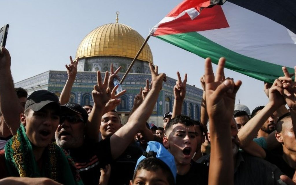 Palestinian Muslims wave a national flag and flash the victory gesture in front of the Dome of the Rock atop the Temple Mount compound in Jerusalem's Old City on July 27, 2017. ( AFP PHOTO / AHMAD GHARABLI)