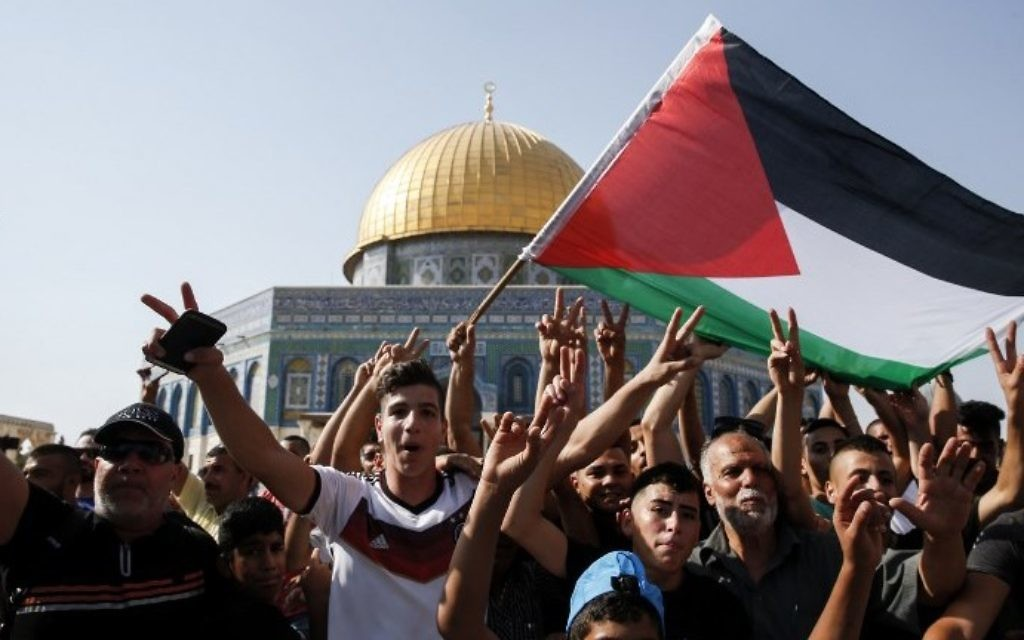 Worshipers wave a Palestinian flag and flash the victory gesture in front of the Dome of the Rock on the Temple Mount on July 27, 2017. (AFP Photo/Ahmad Gharabli)