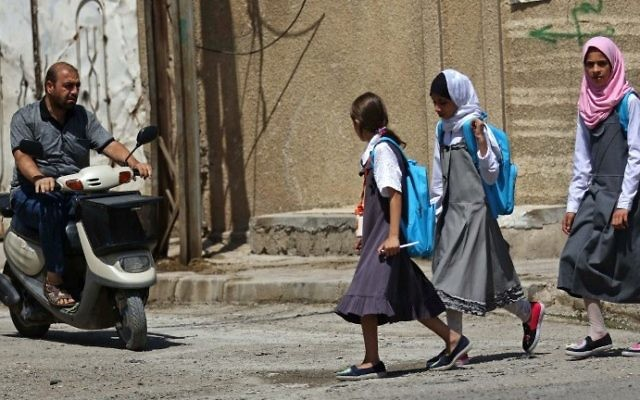 Iraqi girls walk to school in west Mosul on July 27, 2017. (AFP/Safin Hamed)