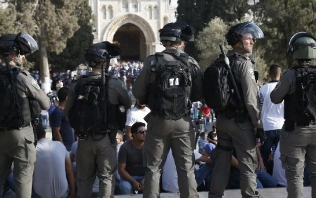 Israeli security forces stand before Palestinians on the Temple Mount in Jerusalem on July 27, 2017, with the Al-Aqsa mosque appearing in the background. (AFP PHOTO / AHMAD GHARABLI)