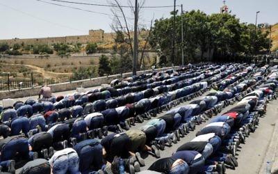 Muslim worshipers pray outside Jerusalem's Old City near the Lions' Gate on July 28, 2017. (AFP PHOTO / MENAHEM KAHANA)