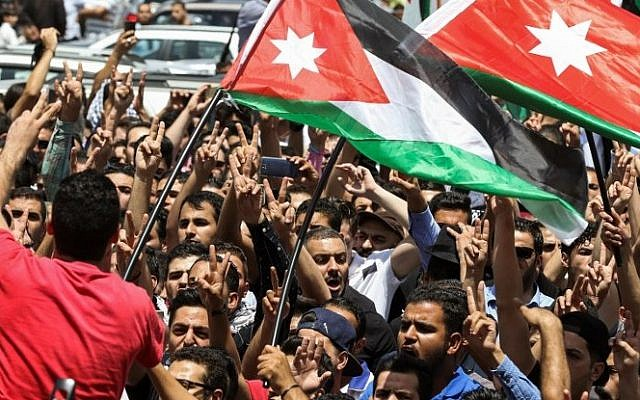 Jordanian protesters wave national flags and chant slogans during a demonstration near the Israeli embassy in the capital Amman on July 28, 2017, calling for the shutting down of the embassy, expelling the ambassador, and canceling the 1994 peace treaty with Israel. (AFP Photo/Khalil Mazraawi)