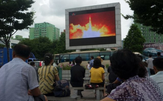 People watch as coverage of an ICBM missile test is displayed on a screen in a public square in Pyongyang on July 29, 2017.(AFP PHOTO / Kim Won-Jin)