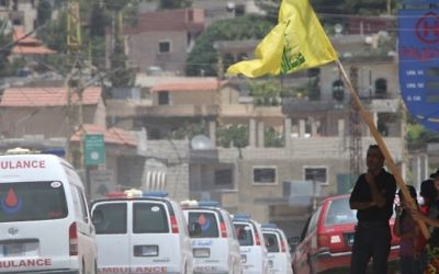 People wave a flag of the Lebanese terror group Hezbollah as the group's ambulance convoy drives past, carrying bodies of fighters killed in week-long clashes in the Jurud Arsal border region, as part of a ceasefire deal. (AFP/Stringer)