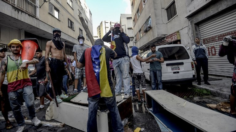 Anti-government activists attack and set fire to a police station during a protest against the election of a Constituent Assembly in Caracas on July 30, 2017. (AFP Photo/Juan Barreto)