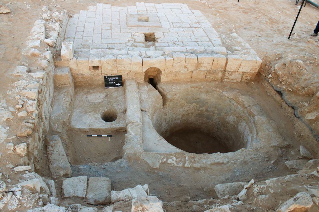 The wine press in Ramat Negev is intermeshed with a building, as seen in this summer 2017 photo. (Davida Dagan, Israel Antiquities Authority)