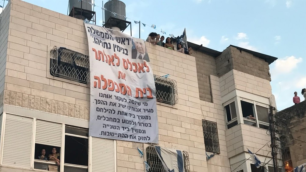 A July 26,2017 photo showing a banner hung from the Machpela House in Hebron calling on Prime Minister Benjamin Netanyahu not to evict the families inside. (Jacob Magid)