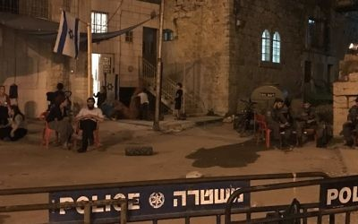 Squatters of the Machpela House in Hebron sit outside the building as Border Police look on, July  26, 2017. (Jacob Magid/Times of Israel)