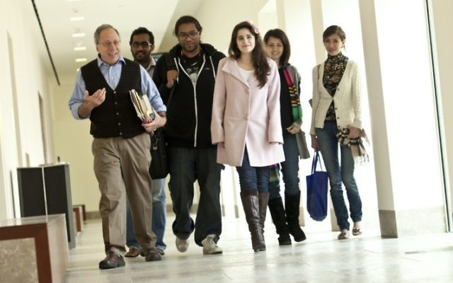 Gary Wasserman, left, strolls through a corridor on the Georgetown campus in Qatar with his students in 2012. (Georgetown University-Qatar)