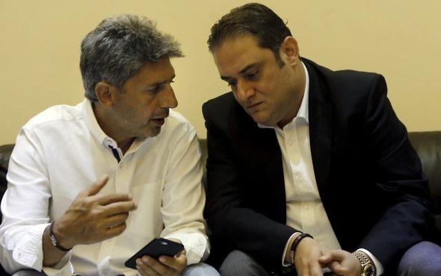 Ziad Zakka, left, brother of Nizar Zakka who is imprisoned in Iran, speaks with his brother's lawyer Majed Dimshkiyeh in Beirut, Lebanon, Tuesday, July 18, 2017. (AP/Bilal Hussein)
