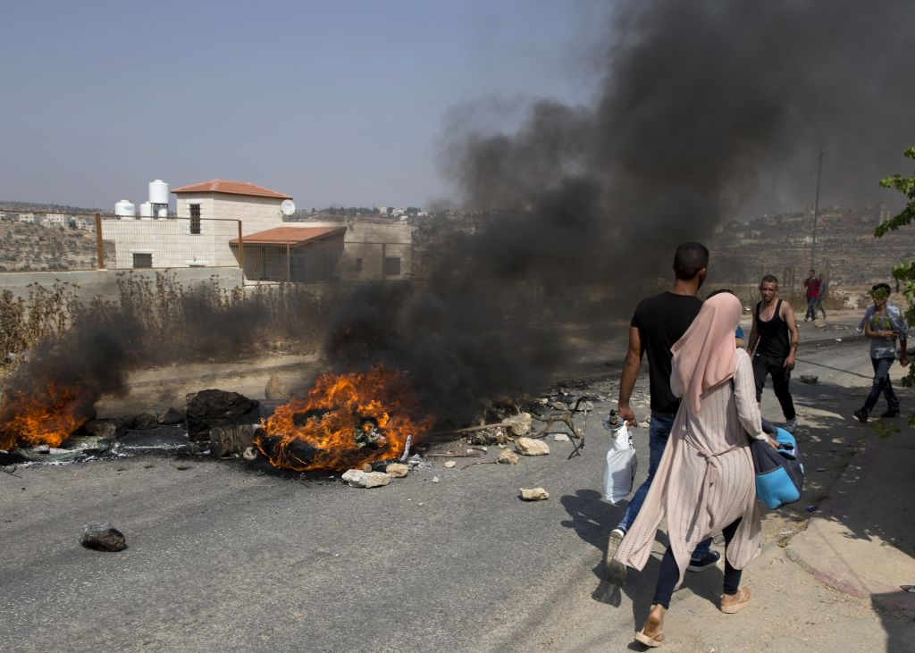 Palestinian protesters burn tires and clash with Israeli soldiers after troops searched and measured family house of Omar al-Abed, 20, perpetrator of Friday's attack at the West Bank settlement of Halamish, in preparation for demolition, in the West Bank village of Kobar, near Ramallah, Saturday, July 22, 2017. (AP Photo/Nasser Nasser)