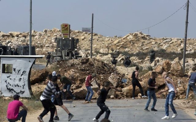 Illustrative: Palestinian protesters throw rocks at Israeli soldiers in the West Bank village of Kobar, while an army bulldozer closes the main road to the area during an operation to prepare the home of a terrorist for demolition on July 22, 2017. (AP Photo/Nasser Nasser)