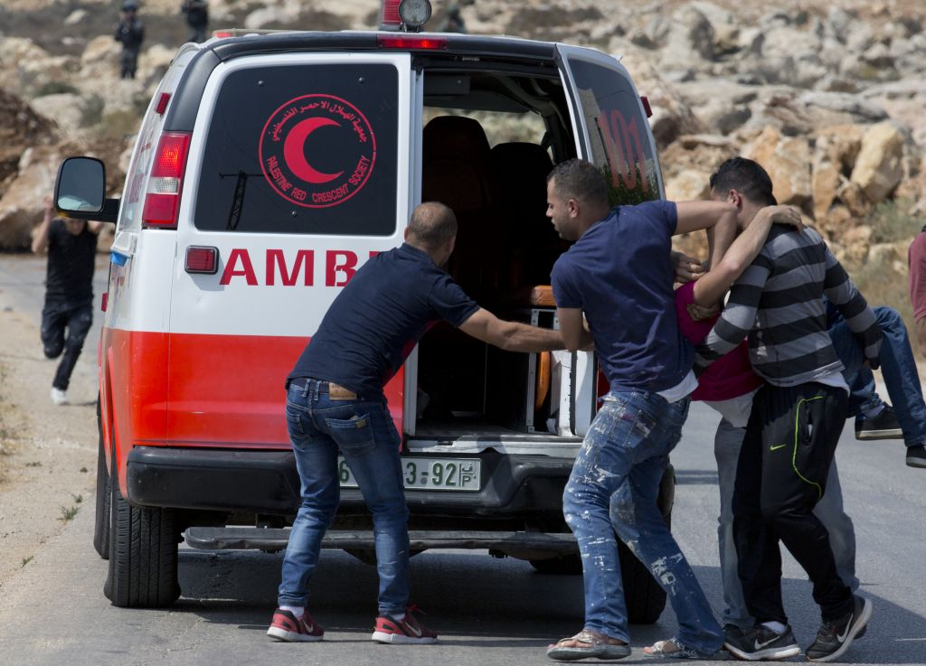 An injured Palestinian protester is evacuated toward an ambulance during clashes with Israeli soldiers after troops searched and measured family house of Omar al-Abed, 20, perpetrator of Friday's attack at the West Bank settlement of Halamish, in preparation for demolition, in the West Bank village of Kobar, near Ramallah, Saturday, July 22, 2017. (AP Photo/Nasser Nasser)