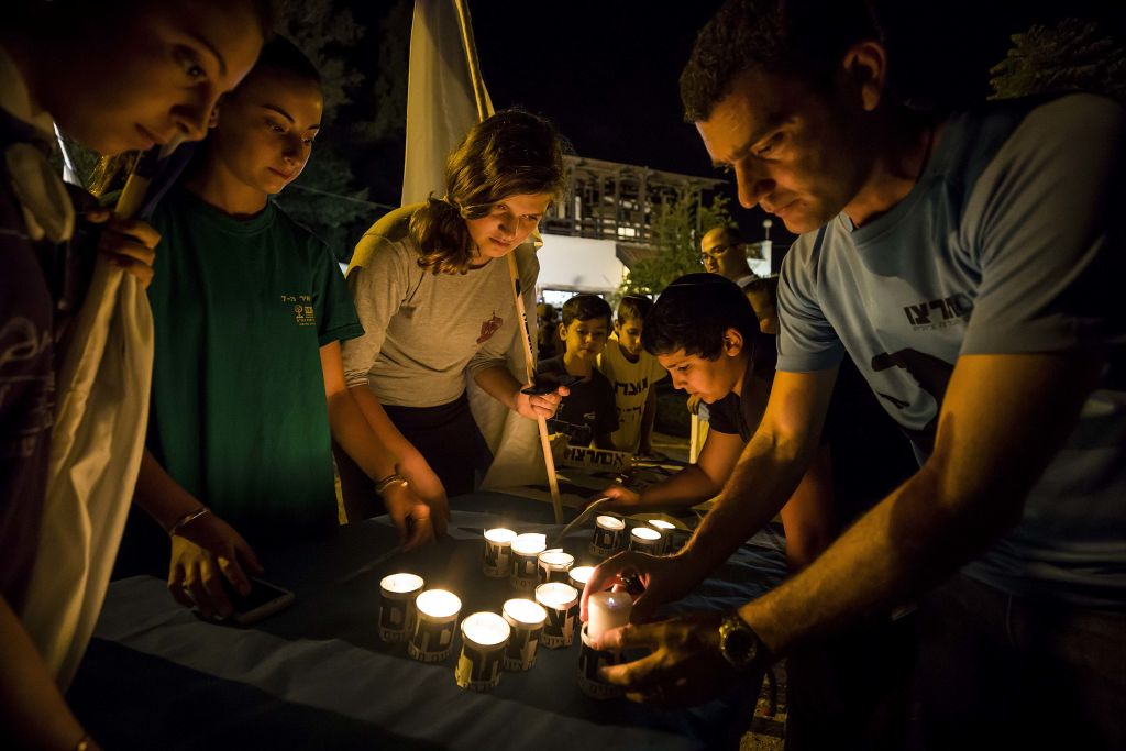 Israelis light candles in the West Bank settlement of Halamish, Saturday, July 22, 2017. (AP Photo/Tsafrir Abayov)
