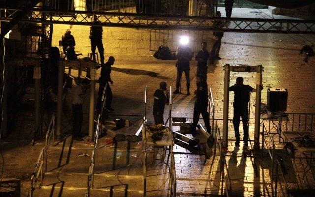 Israeli police officers dismantle metal detectors outside the Temple Mount in Jerusalem's Old City, early Tuesday, July 25, 2017. (AP/Mahmoud Illean)