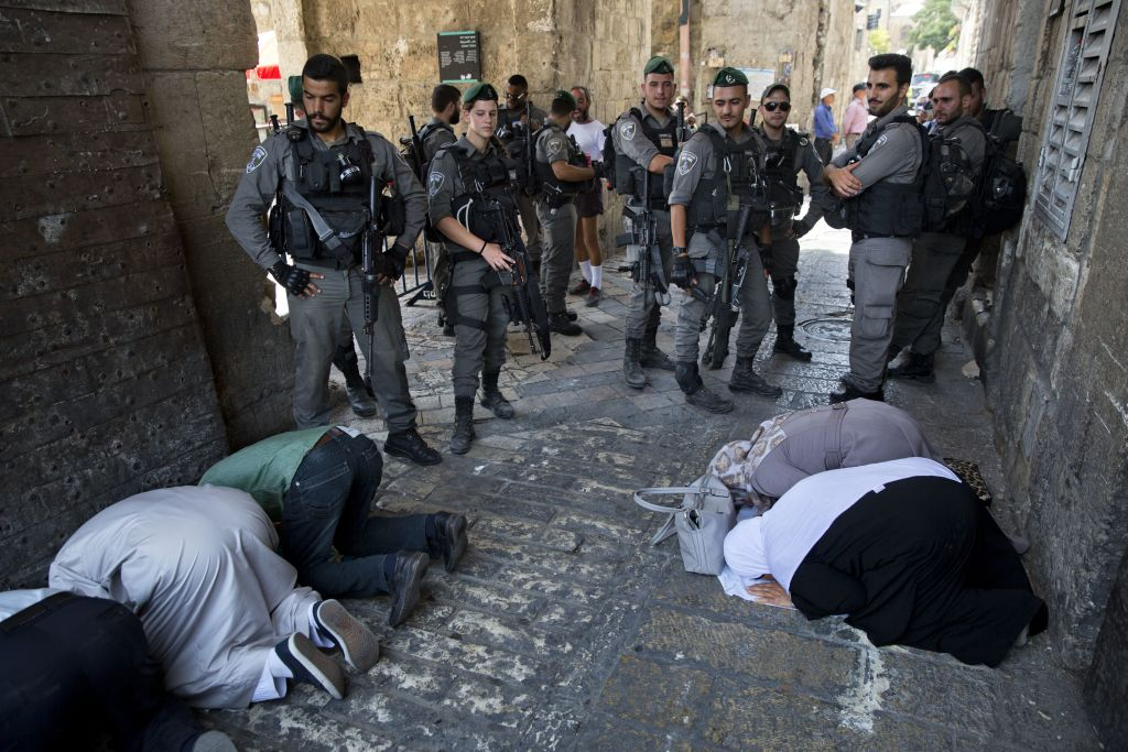 Palestinians pray as Israeli border police officers stand guard at the Lions' Gate in Jerusalem's Old City, Tuesday, July 25, 2017. (AP Photo/Oded Balilty)