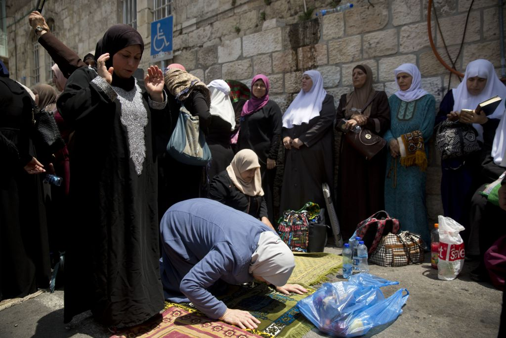 Palestinian women pray near the Temple Mount in Jerusalem's Old City, Tuesday, July 25, 2017. (AP Photo/Oded Balilty)