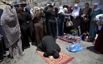 Palestinian women pray near the Lions Gate in Jerusalem's Old City, Tuesday, July 25, 2017.  (AP Photo/Oded Balilty)