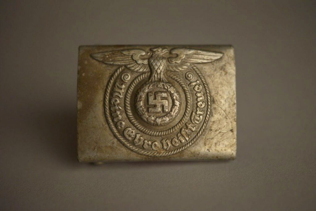 This photo made available by the Aushwitz Museum on Wednesday, July 26, 2017 shows an SS belt buckle from their exhibition. (Pawel Sawicki/Aushwitz Museum via AP)