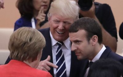 German Chancellor Angela Merkel, front, talks with US President Donald Trump, centre, and France's President Emmanuel Macron prior to the first working session on the first day of the G-20 summit in Hamburg, northern Germany, Friday, July 7, 2017. (AP Photo/Markus Schreiber)