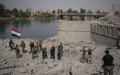 Iraqi Special Forces soldiers celebrate after reaching the bank of the Tigris river as their fight against Islamic State militants continues in parts of the Old City of Mosul, Iraq, Sunday, July 9, 2017. (AP/Felipe Dana)