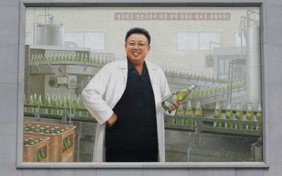 In this July 26, 2017, photo, a mural of the late North Korean leader Kim Jong Il in a white lab coat holding up a bottle of beer is seen at the entrance of the Taedonggang Brewery in Pyongyang, North Korea. (AP Photo/Wong Maye-E)
