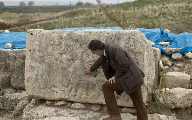 Nicolo Marchetti, a professor of archaeology and art history of the Ancient Near East at the University of Bologna, describes engravings on a stone at a site outside Karkemish, Turkey, meters away from the Turkey-Syria border and the Syrian city of Jarablous, Saturday, Nov. 15, 2014. (AP Photo/Vadim Ghirda)