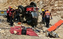Medics and firefighters pull two men out of a truck that overturned along a highway, north of the city of Eilat, on July 13, 2017. (Magen David Adom)