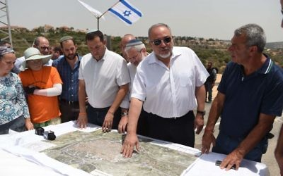 Defense Minister Avigdor Liberman presents his plan to allow Palestinians to expand the West Bank city of Qalqilya into area currently controlled by Israel, during a tour of the Maale Shomron settlement on July 12, 2017. (Eden Moldavski/Defense Ministry)