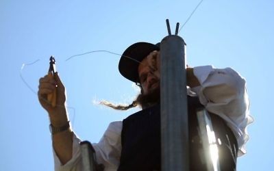 Illustrative: An ultra-Orthodox man erecting an eruv wire, near the Gilo neighborhood in south Jerusalem, on August 14, 2009. (Nati Shohat / FLASH90/File)