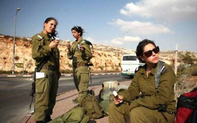 Israeli soldiers eating ice cream while waiting for a bus near Ramallah on October 1, 2009. (Matanya Tausig/Flash90)
