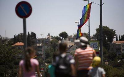 Israelis pass by rainbow flags in Jerusalem ahead of the Jerusalem Pride Parade, on July 31, 2013 (Yonatan Sindel / Flash90)