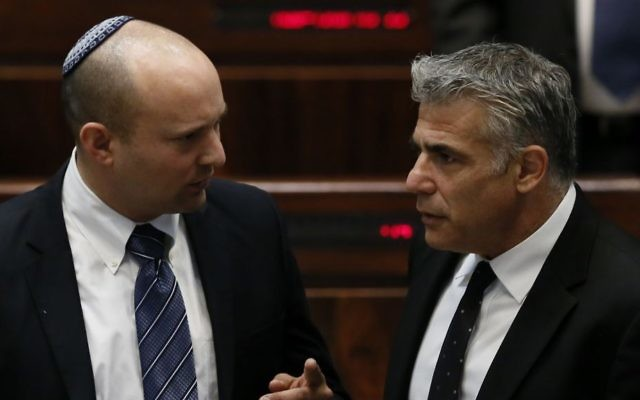 Jewish Home chair Naftali Bennett (L) speaks with Yesh Atid chair Yair Lapid in the Knesset plenum, March 11, 2014. (Miriam Alster/Flash90)