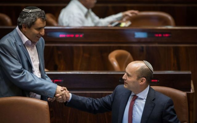 Jewish Home chair Naftali Bennett (R) shakes hands with Minister for Jerusalem Affiars Zeev Elkin after a vote on the so-called Regulation Bill, a controversial bill that seeks to legitimize illegal West Bank outposts, December 7, 2016. (Hadas Parush/Flash90)