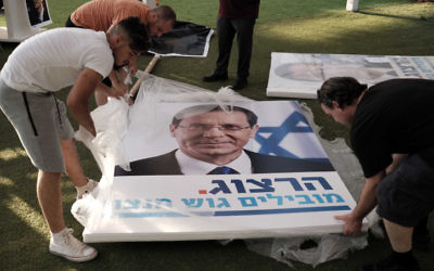 Workers holding large campaign posters during  a rally supporting Labor party leader Isaac Herzog in Tel Aviv on June 26, 2017, (Tomer Neuberg/Flash90)