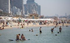 Israelis and tourists enjoy the beach in Tel Aviv, on a hot summer day, July 3, 2017. A new survey finds that they are optimistic and largely satisfied with their lives. (Miriam Alster/ FLASH90)