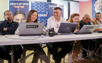 Labor leadership candidate Avi Gabbay, with Labor party members Stav Shaffir and Shelly Yachimovich, make phone calls to potential voters ahead of the second round of the Labor party primaries in Tel Aviv, on July 9, 2017. (Flash90)