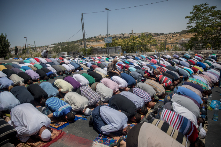 Muslim worshippers pray on a street outside the Lions Gate near Jerusalem's Temple Mount on July 14, 2017, after the site was closed following an attack near the holy site in which three Arab Israelis shot and killed two Israeli police officers. (Yonatan Sindel/Flash90)