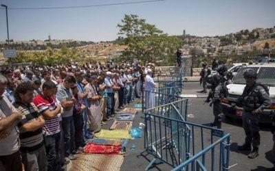 Muslims pray as Border Police officers stand guard during Friday prayers in the East Jerusalem neighborhood of Wadi Joz, July 14, 2017. (Yonatan Sindel/Flash90)