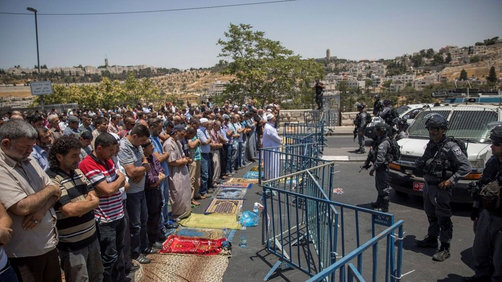 Muslims pray as Border Police officers stand guard during Friday prayers in the East Jerusalem neighborhood of Wadi al-Joz, July 14, 2017. (Yonatan Sindel/Flash90)
