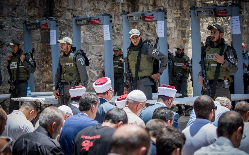 Waqf officials lead Muslim prayers outside the Temple Mount in Jerusalem's Old City on July 16, with metal detector gates in the background. (Yonatan Sindel/Flash90)