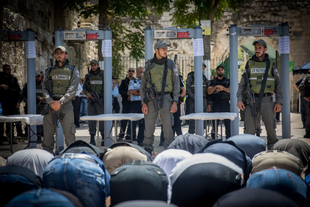 Muslims pray in front of metal detectors placed outside the Temple Mount, in Jerusalem's Old City, July 16, 2017. (Yonatan Sindel/Flash90)