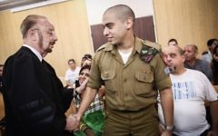 Elor Azaria shake hands with his attorney Yoram Sheftel before the start of a court hearing at the IDF's Tel Aviv headquarters on July 17, 2017. (Miriam Alster/Flash90)
