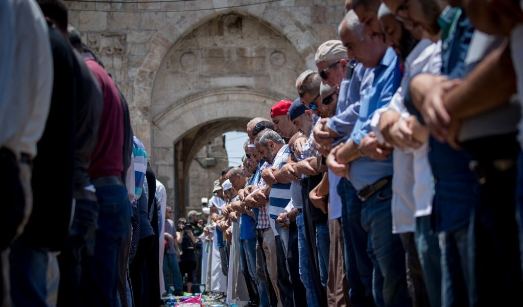 Muslim worshipers perform noon prayers the Lion's Gate, outside the Temple Mount, in Jerusalem's Old City on July 19, 2017. (Yonatan Sindel/Flash90)