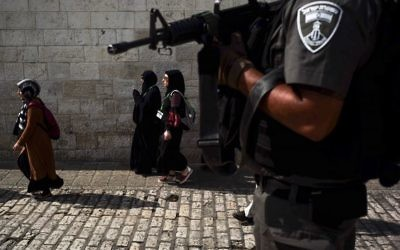 A border policeman oversees Muslim worshipers leaving the Temple Mount in Jerusalem's Old City, July 20, 2017. (Sebi Berens/Flash90)