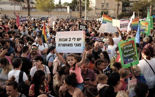 A girl carries a sign reading 'I have two mothers and I'm happy' as thousands protest in support of the right of LGBT couples to adopt children in Tel Aviv on July 20, 2017. (Tomer Neuberg/FLASH90)