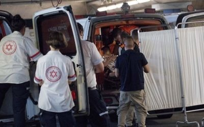 Medics wheel a woman who was injured during a stabbing attack in the West Bank settlement of Halamish into the emergency room of the Shaare Zedek Medical Center in Jerusalem on July 21, 2017. (Yonatan Sindel/Flash90)
