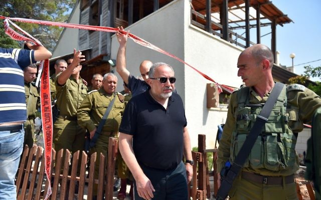 Defense Minister Avigdor Liberman, center at the site of a terror attack in the settlement of Halamish, where three Israelis were murdered and one seriously injured by a Palestinian in a stabbing attack. July 22, 2017. (Hermoni/Ministry of Defense)