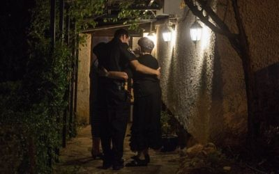 A policeman embraces a woman who lives near the home where three Israelis were killed in a terror stabbing a day earlier, in the settlement of Halamish, West Bank, on Saturday, July 22, 2017 (Hadas Parush/FLASH90)