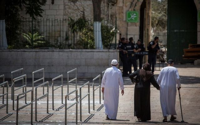 Police officers guard at an entrance to the Temple Mount, as a group of Muslims walk by metal railings installed at the site after a recent terror attack on July 25, 2017. (Hadas Parush/Flash90)